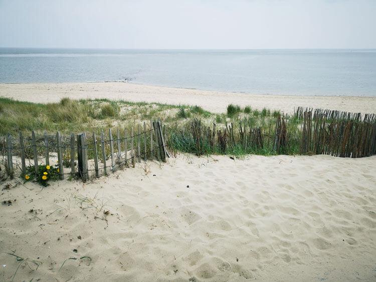 Düne mit Sandstrand und Zaun