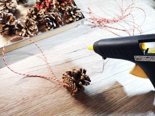 Weihnachtsbaumschmuck basteln aus Tannenzapfen - Aufhänger mit Heißklebepistole anbringen